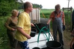 Die Eimer werden mit Schlauch gefüllt